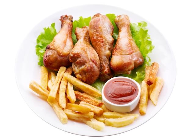 흰색에 고립 된 감자 튀김과 구운 닭 다리의 접시