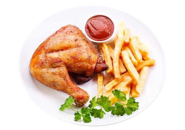 흰색 절연 감자 튀김과 구운 된 닭 다리의 접시