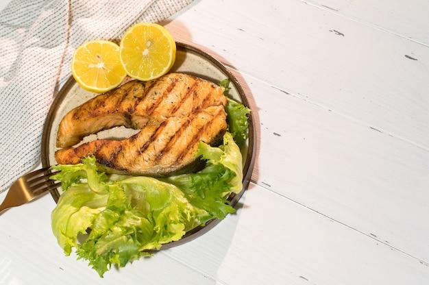 木製のテーブルにサラダとサーモンステーキのグリルのプレート。上面図