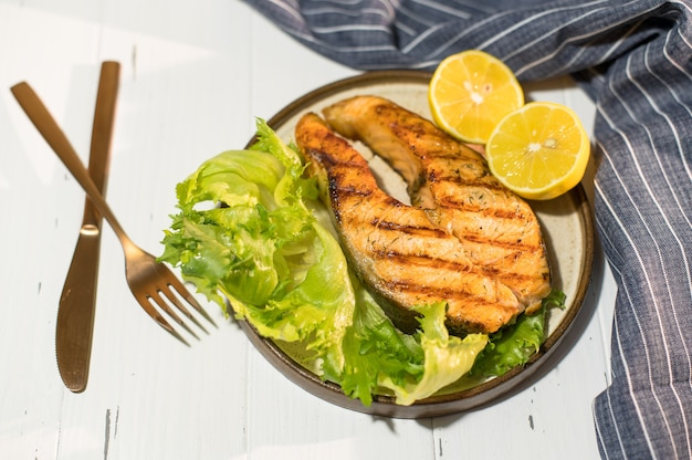 青いナプキンと木製のテーブルの上にサラダとサーモンステーキのグリルのプレート。