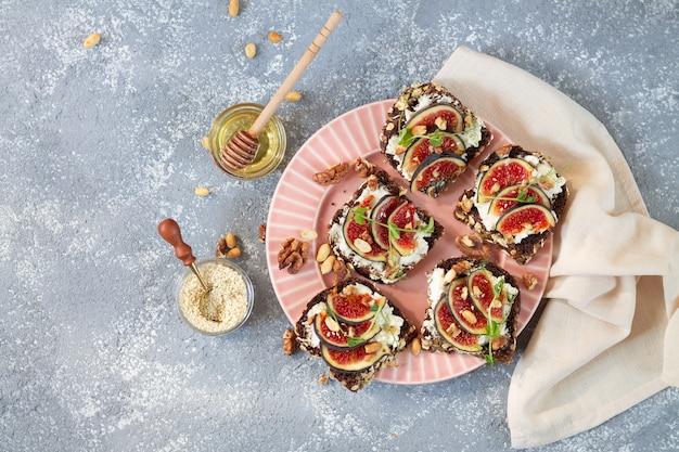 健康的な前菜のプレート。イチジク、チーズ、ゴマ、小屋、蜂蜜を上から乗せたブルスケッタ