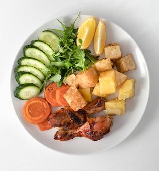 Тарелка здорового питания запеченные куриные крылышки. запеченные овощи для салата. в белой тарелке на белом мраморном фоне.