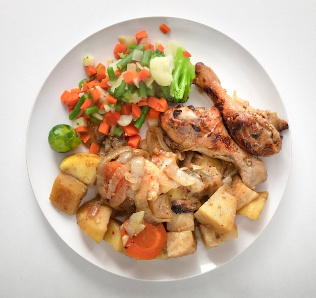 건강 식품 접시 구운 닭 날개. 구운 야채 샐러드. 흰색 대리석 배경에 흰색 접시.