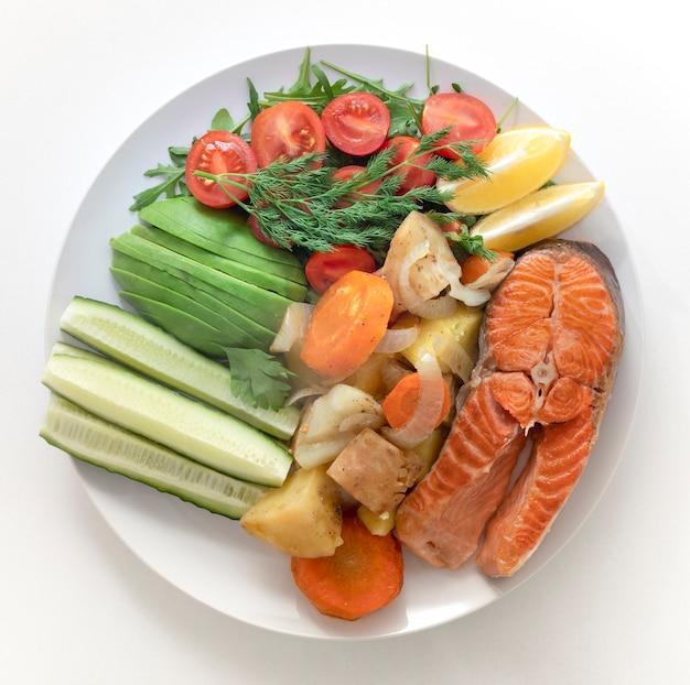 흰색 접시에 건강 식품 튀긴 생선, 연어, 샐러드 접시. 흰색 대리석 배경.
