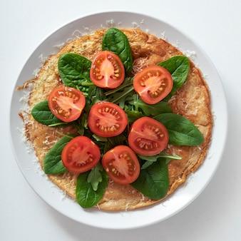 健康食品のプレート緑と野菜のオートミールパンケーキ。健康的な朝食。白い大理石の背景に白いプレートで。
