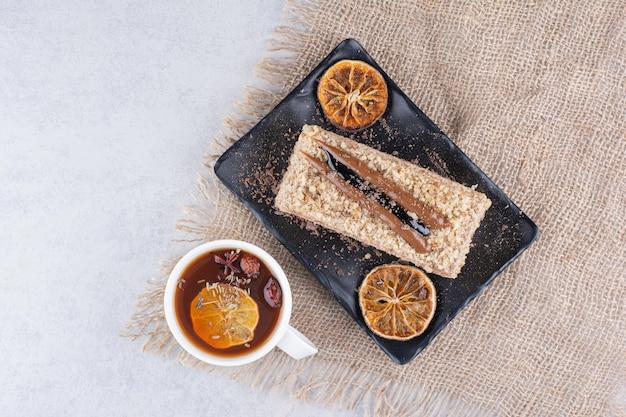 黄麻布にフルーツティーと自家製ケーキのプレート。高品質の写真