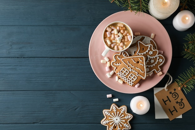 自家製クリスマスクッキー、コーヒー、木製のテーブル、青、テキスト用のスペースにマシュマロのプレート。上面図