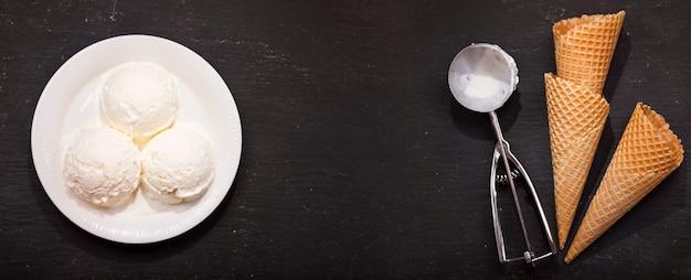 Тарелка совков мороженого и вафельных рожков на темном фоне. вид сверху с копией пространства, баннер