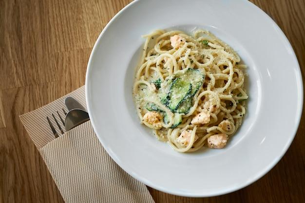 Тарелка итальянской пасты феттучини в сливочном соусе с лососем и цукини на столе