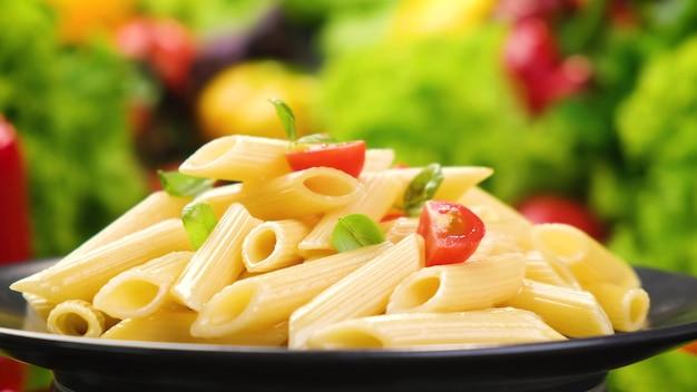 토마토와 바질 잎을 가진 이탈리아 펜네 rigate 파스타 접시,
