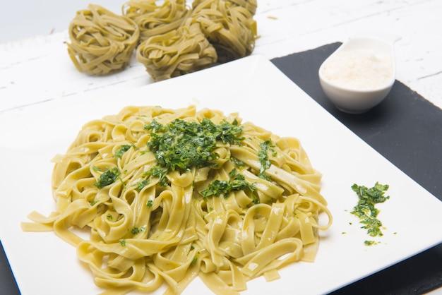 Тарелка итальянской пасты тальятеле с тертым сыром, подаваемая на стол