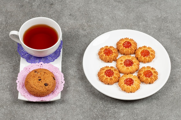 一杯のお茶とチップクッキーとゼリービスケットのプレート