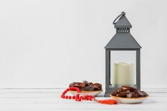 赤い祈りビーズと白い背景に対してランタンホルダーのキャンドルとジューシーな日付のプレート