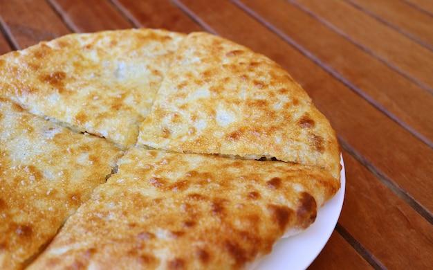 Svaneti 지역 조지아의 매운 쇠고기 전통 요리로 채워진 kubdari 평평한 빵 접시