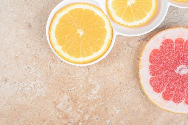 大理石の背景にレモンとグレープフルーツのスライスのプレート。