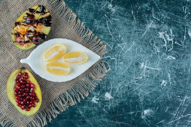 Тарелка лимонов и фруктовых салатов на мешковине.