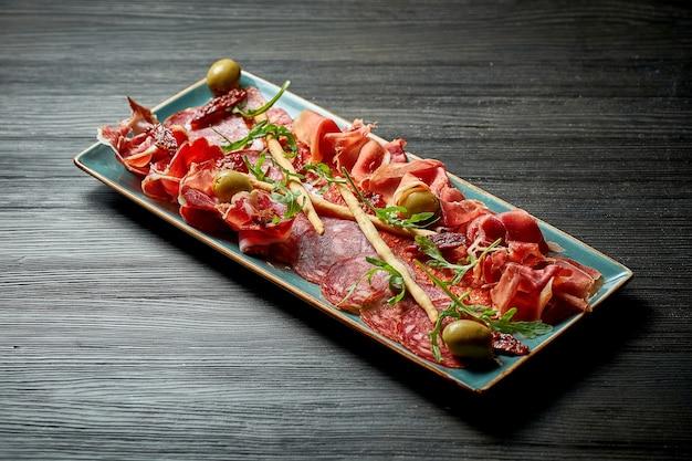 Тарелка мясных закусок с салями, хамоном в синей тарелке на деревянном фоне