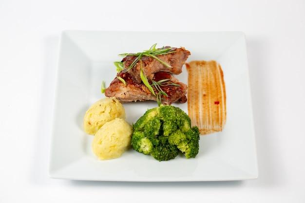 Тарелка мяса с соусом барбекю, картофельное пюре и брокколи