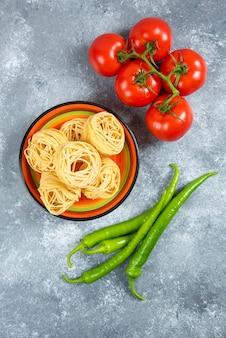 국수, 칠리 페 퍼와 대리석 배경에 토마토 접시.