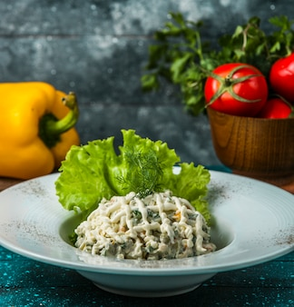 Тарелка салата оливье, украшенная листьями салата и укропа