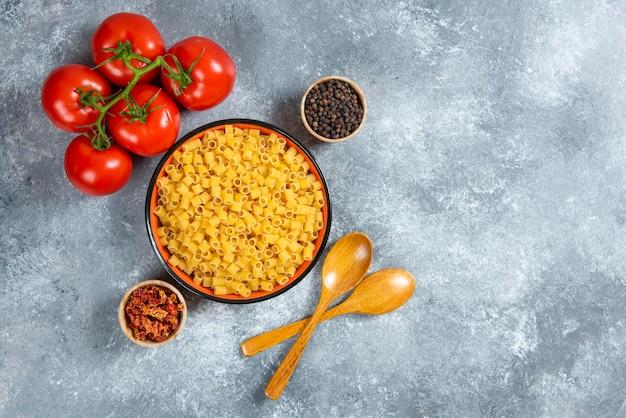 Тарелка макаронных изделий и миска помидоров на мраморном фоне.