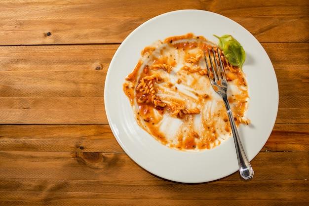 Тарелка макарон с соусом закончена и грязная на деревянном столе. вид сверху