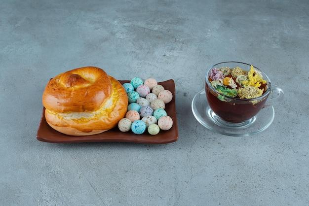 대리석에 차 한잔과 함께 과자와 사탕 접시.