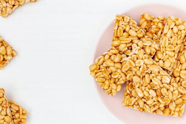白い木製の背景にピーナッツのもろいキャンディーピースのプレート。トップビュー、コピースペース