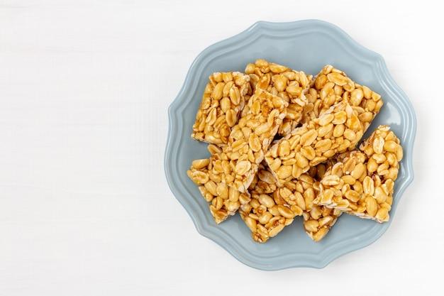 ピーナッツのもろいキャンディーのプレート。白い木製の背景の平面図です。