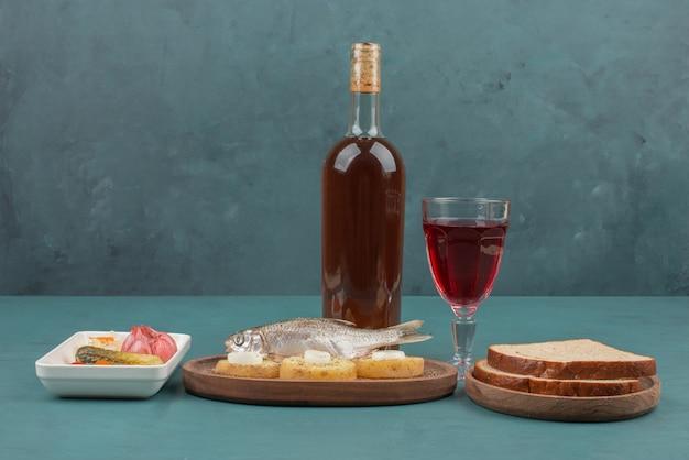 Тарелка маринованных овощей, рыбы, ломтиков хлеба и красного вина на синем столе.