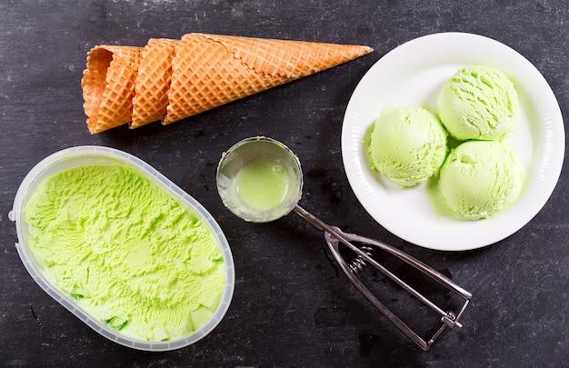 Тарелка ложек фисташкового мороженого и вафельных рожков на темноте, вид сверху