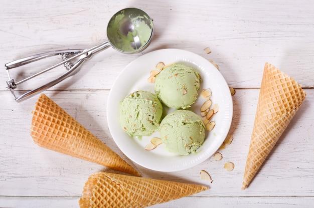 나무 테이블에 피스타치오 아이스크림 국자와 와플 콘 접시, 평면도