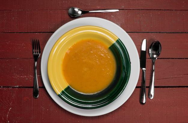 赤い木製のテーブルの上のカボチャスープのプレート