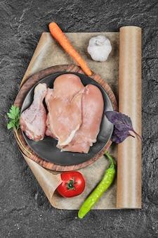 Тарелка сырых куриных частей с помидорами и морковью на темной поверхности