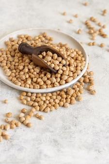白いテーブルの上の生の乾燥ひよこ豆のプレートをクローズアップ