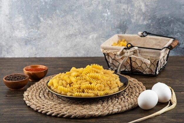 Тарелка сырых фузилли, приправ и сырых яиц на деревянной поверхности.