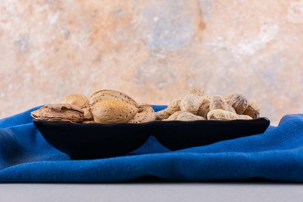 Тарелка сырого очищенного миндаля и арахиса на синей ткани. фото высокого качества