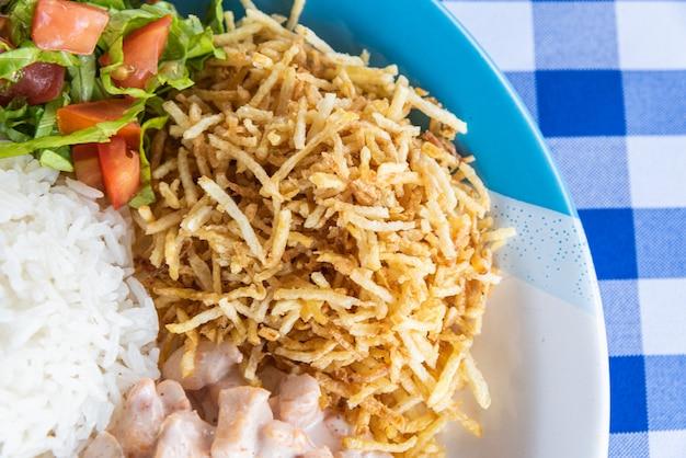 Тарелка риса, бефстроганов, картофель и томатный салат - типичная бразильская еда