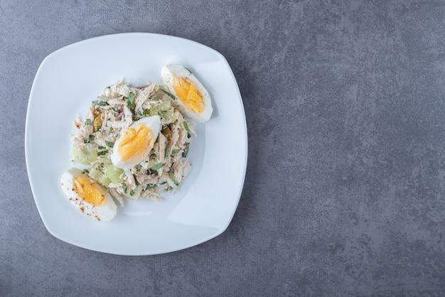 石のテーブルの上にゆで卵とサラダのプレート。
