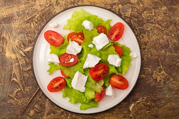 チェリートマト、柔らかいブリンドザチーズ、レタスの葉のサラダのプレート。オリーブオイルのドレッシング。ダイエット料理。上面図