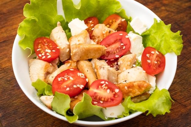 チキン、トマト、ソフトチーズチーズのサラダプレート。オリーブオイルとゴマのドレッシング。ダイエット食品。木製の背景