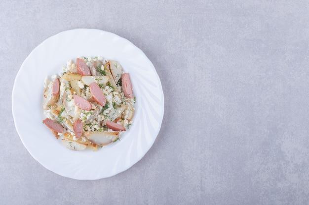 Тарелка салата с сосисками на каменном фоне.