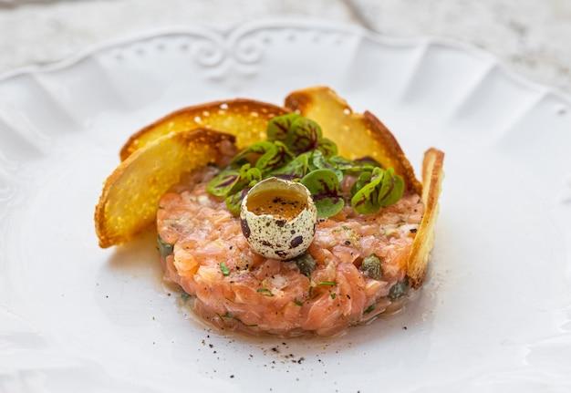 날달걀과 구운 빵 조각을 곁들인 연어 타르타르 접시를 닫습니다.