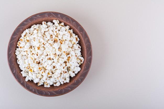 白い背景の上の映画の夜のための塩味のポップコーンのプレート。高品質の写真