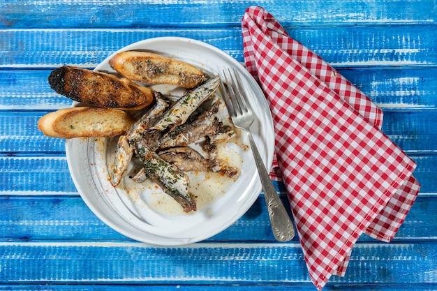 素朴な木製のテーブルの上にパセリとパプリカとトーストを添えたイワシのオイルプレート。上面図、