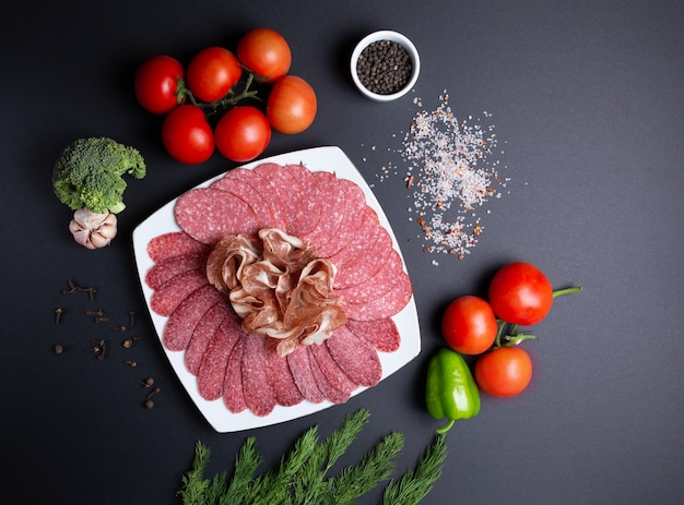 Тарелка колбасы и мяса, на черном, с помидорами, укропом, чесноком и брокколи