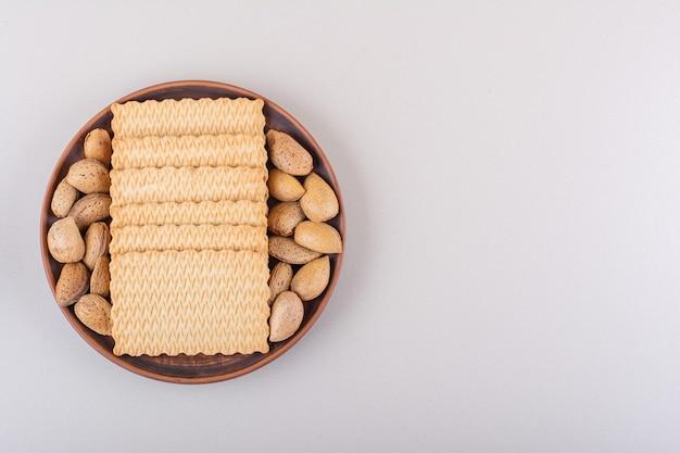 Тарелка очищенного органического миндаля и печенья на белом фоне. фото высокого качества