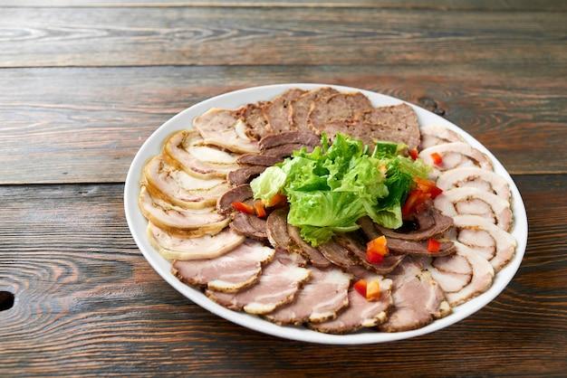 Тарелка нарезанного ассорти из мяса украшена нарезанным салатом на деревянном столе. copyspace еда есть вкусная вкусная еда, ужин, закуска, обед, ресторан, кафе, съедобные овощи.