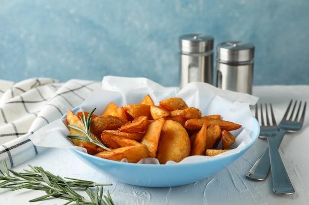 Тарелка ломтики печеного картофеля, розмарина, соли, вилки на белом столе, на синем. крупный план
