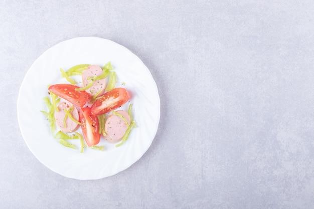 Тарелка нарезанных колбас и помидоров на каменном фоне.